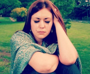 A girl in tears. Facial emotions of a young woman sitting alone in a park.